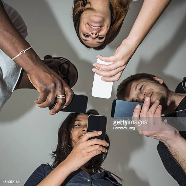 Four young people holding mobile phones