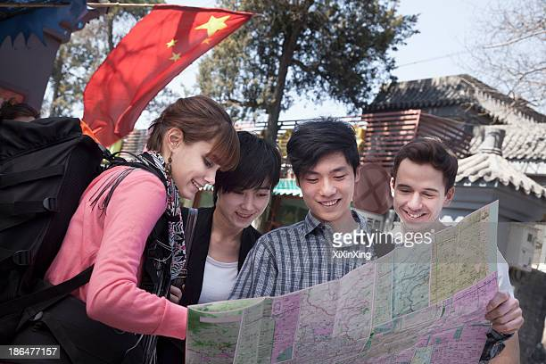 Four young people looking at map.