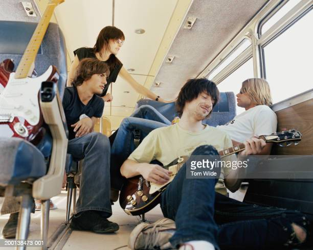 Four young people on bus, man playing guitar