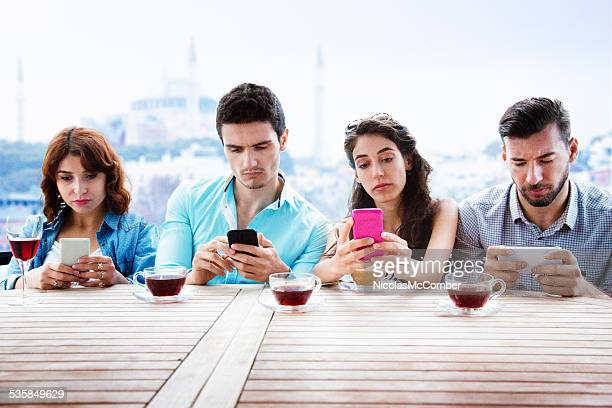 Four young people on their phones with unhappy expressions