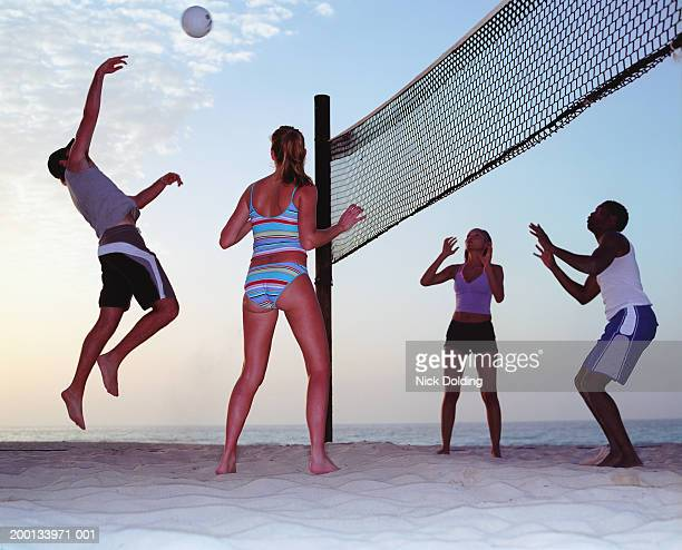 Four young people playing beach volleyball