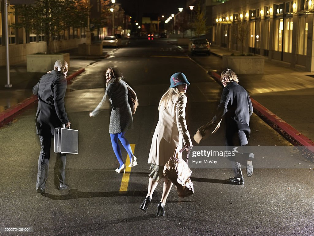 Four young people running down road, looking over shoulders, rear view : Stock Photo