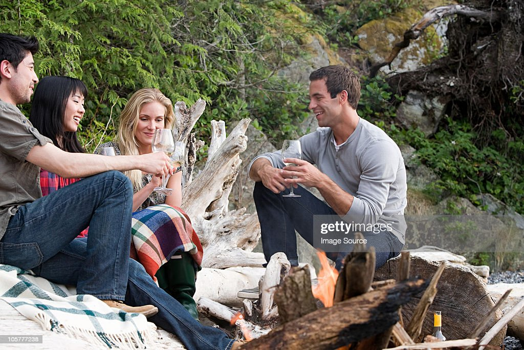 Four young people sitting around campfire : Stock Photo