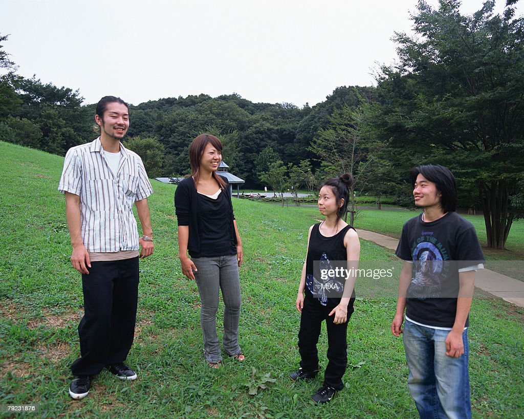 Four young people standing in fields : Stock Photo