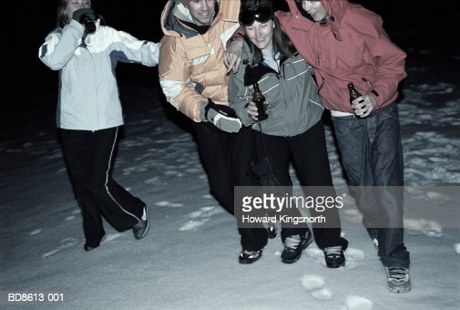 Four young people walking in snow at night, drinking beer : Stock Photo