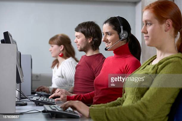 Four young persons in a row working at computer