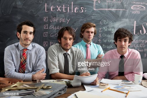 Four young professional males with chalkboard : Stock Photo