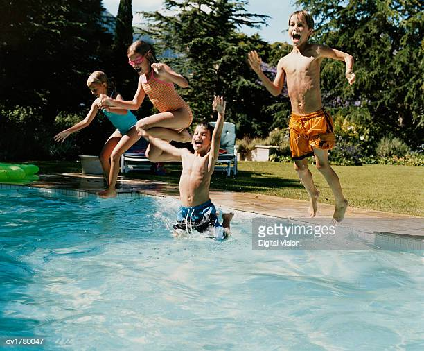 Four Young Teens Jumping in a Swimming Pool