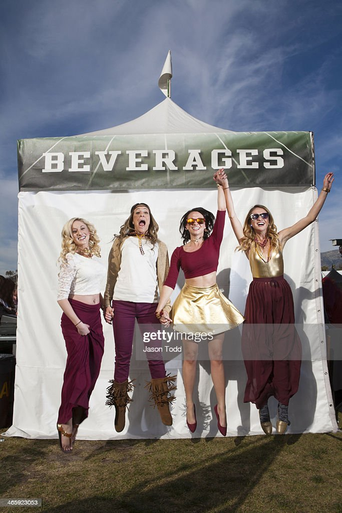 four young woman jumping at tailgate party : Stock Photo