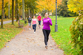 Four young woman out running together in an autumn park approaching the camera along a footpath as they run a race or train in a healthy outdoors lifestyle concept