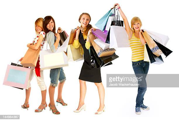 Four young women carrying shopping bags