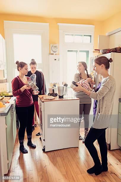 Vier Zimmergenossinnen Reinigung ein Saftpresse in Ihr appartement Küche.