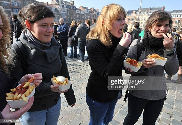 Four young women eat French fries on the 'Chips Revolution' Day' in Leuven on February 172011 Belgium today snatched Iraq's dubious record as the...