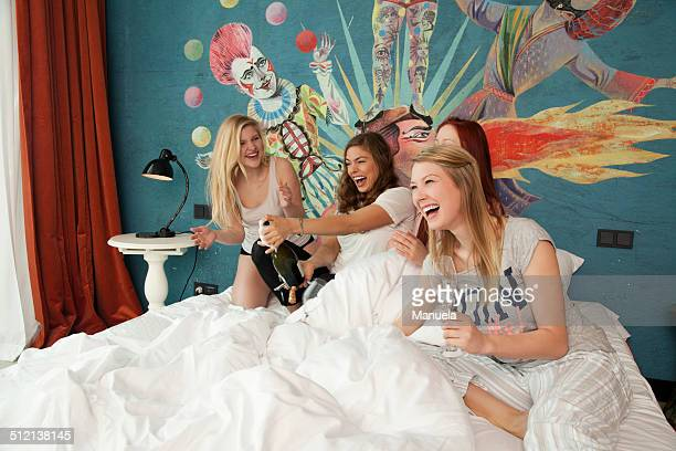 Four young women friends uncorking champagne on hotel bed