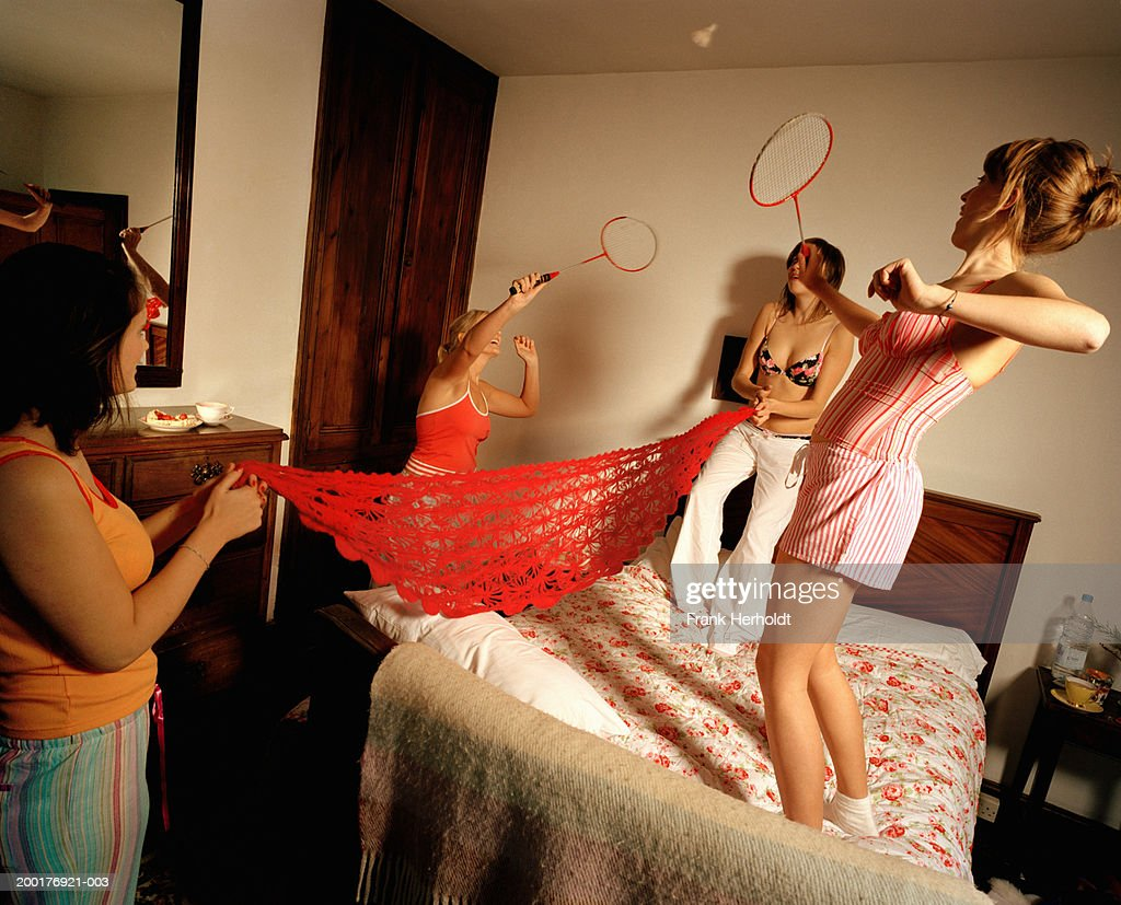 Four young women playing badminton in bedroom : Stock Photo