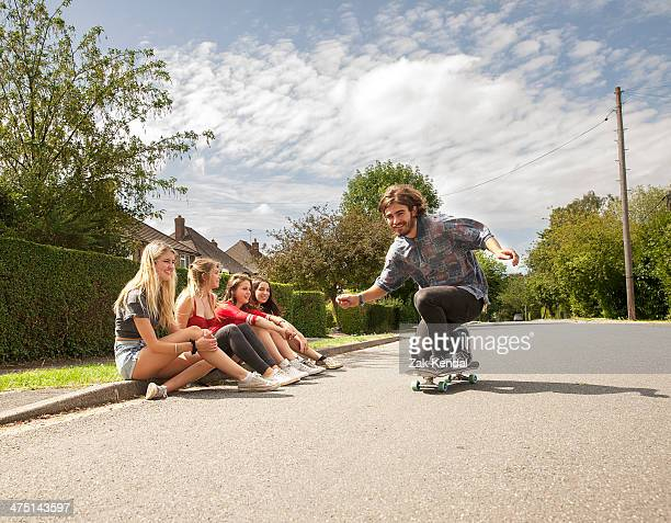 Four young women sitting on kerb watching skateboarder