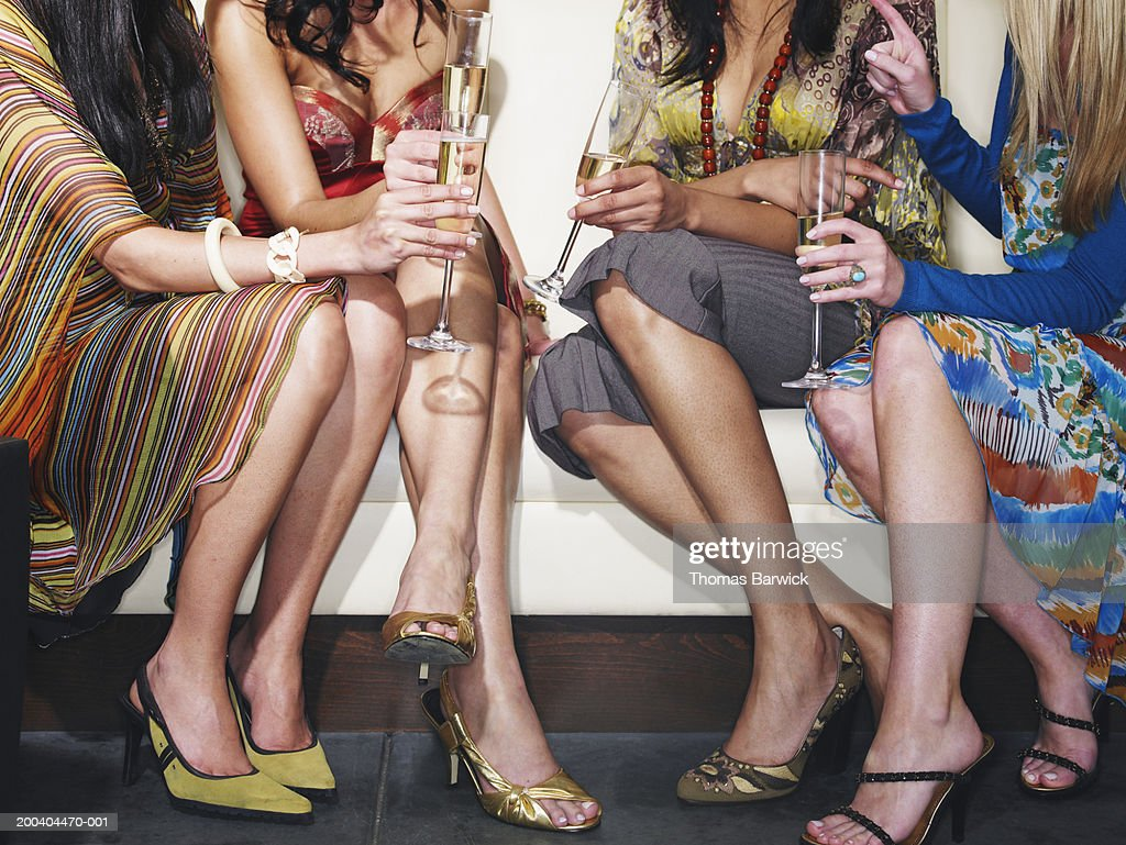 Four young women sitting on sofa, drinking champagne, low section