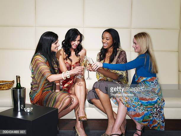 Four young women toasting with champagne in nightclub, smiling