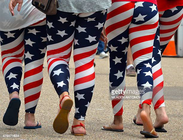 Four young women wear US flag leggings marking the Independence Day as they walk on Pennsylvania Avenue in Washington DC on July 4 2015 / AFP /...
