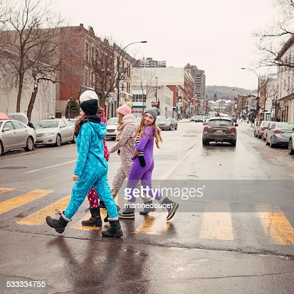 Four young women wearing onesies crossing the street in winter.