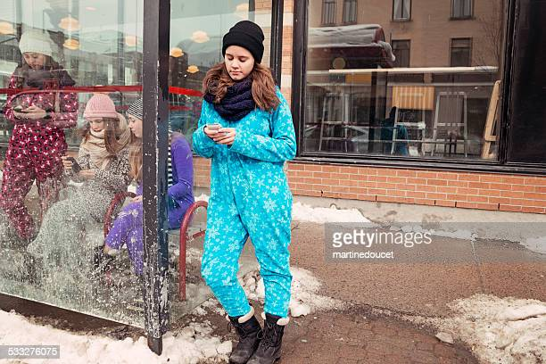 Four young women wearing onesies waiting for bus in winter.