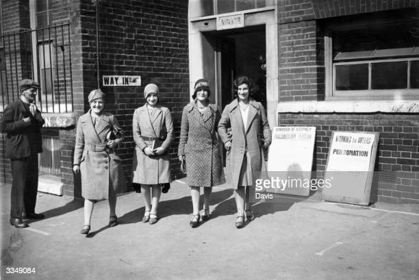 Four young women wearing the cloche hats typical of the 'flapper' era leave the polling station of the London Borough of Stepney after voting in the...