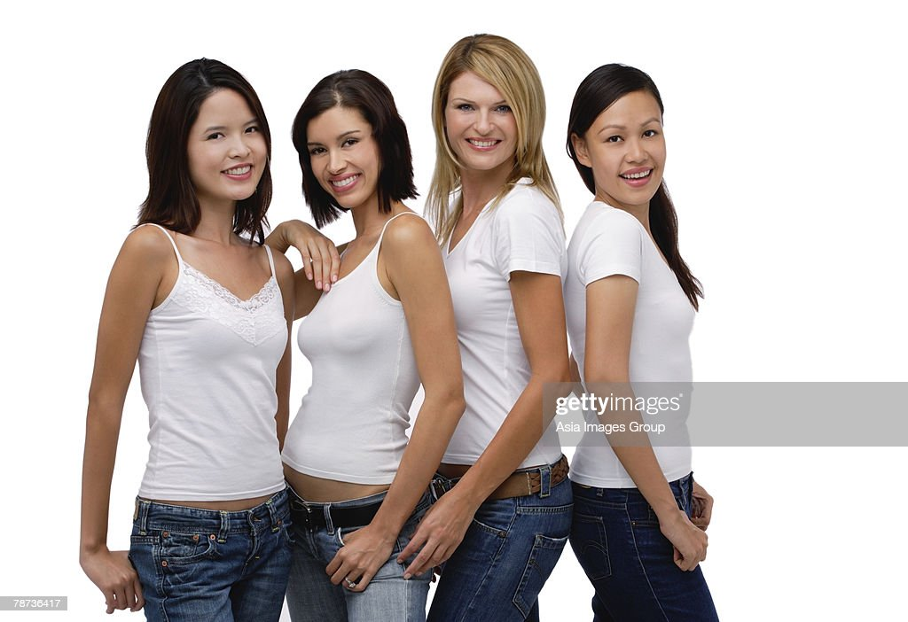 Four young women wearing white shirts and jeans, smiling at camera : Stock Photo