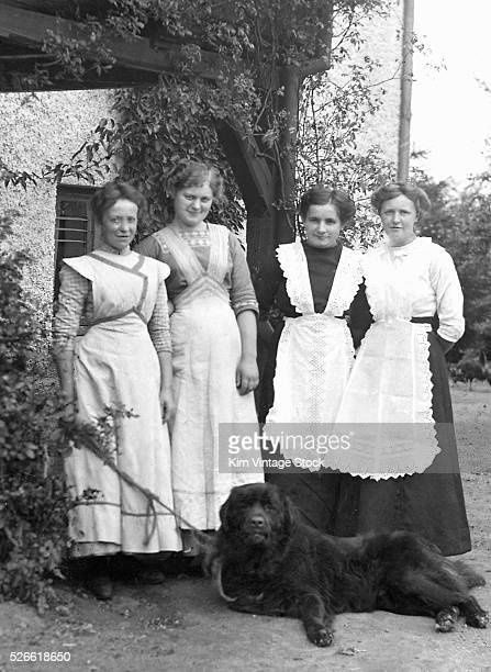 Four young women working as household staff stand together with a lounging Newfoundland dog