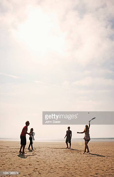 four youngsters playing beach tennis together
