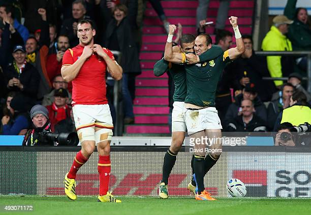 Fourie Du Preez of South Africa is congratulated by Bryan Habana of South Africa for scoring the winning try as Captain Sam Warburton of Wales looks...