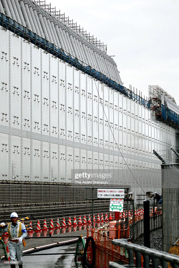 A four-meter-tall steel plate is moved into position to raise the height of the breakwater at Chubu Electric Power Co's Hamaoka nuclear power plant on December 19, 2013 in Omaezaki, Shizuoka, Japan. Chubu Electric originally completed an 18-meter-tall barrier stretching 1.6 kilometers to protect the plant in December 2012. However, it decided to heighten the structure after a Cabinet Office panel predicted a major quake in a worst-case scenario could trigger a 19-meter tsunami along the Pacific coast.