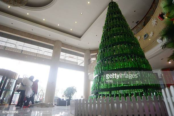 A fourmetrehigh Christmas tree piled up with about 600 beer bottles appears on December 12 2016 in Chenzhou Hunan Province of China Colorful lights...