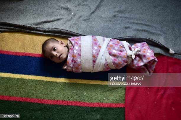 A fourmonths old baby girl is pictured on May 11 2017 at Malakassa refugee camp some 50km north of Athens where around 700 refugees mainly from...
