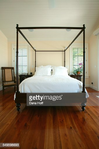A Fourposter Bed In Dark Wood Defines Space In A Master
