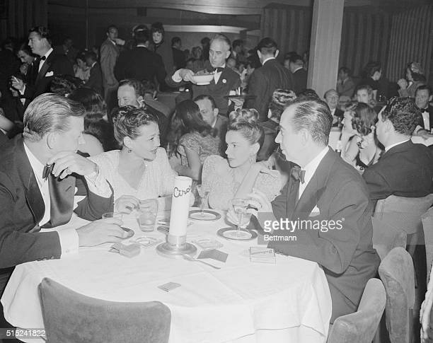 A foursome at Ciro's on Hollywood's Sunset Strip seem interested in Judy Garland's latest story Left to right are Carlton Alsopand his actress wife...