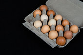 Fourteen chicken eggs in a carton box, isolated on black felt background.