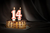 Fourteen years anniversary. Birthday chocolate cake with white burning candles in the form of number Fourteen. Dark background with black cloth