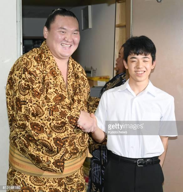 Fourteenyearold shogi star Sota Fujii shakes hands with Mongolian grand champion Hakuho after watching the fourthday battles of the Nagoya Grand Sumo...