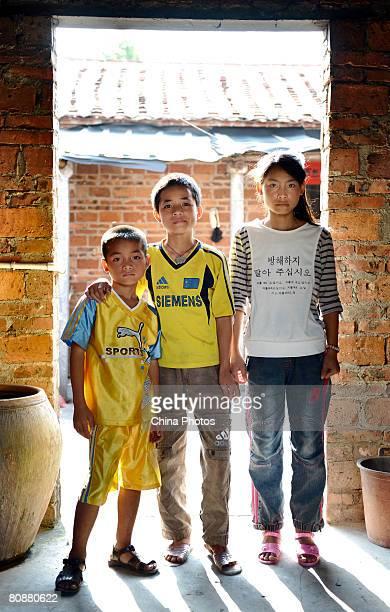 Fourteenyearold Xu Liguan thirteenyearold Xu Dingping and tenyearold Xu Dingwen orphans from the Hebei Village of Fucheng Township poses for pictures...