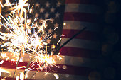 A stock photo of a USA stars and stripes flag with sparklers in the foreground. Perfect for designs and articles about the 4th of July and the USA.