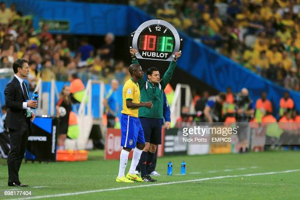 Fourth Official Alireza Faghani holds up the board as Brazil's Ramires prepares to come on as a substitute