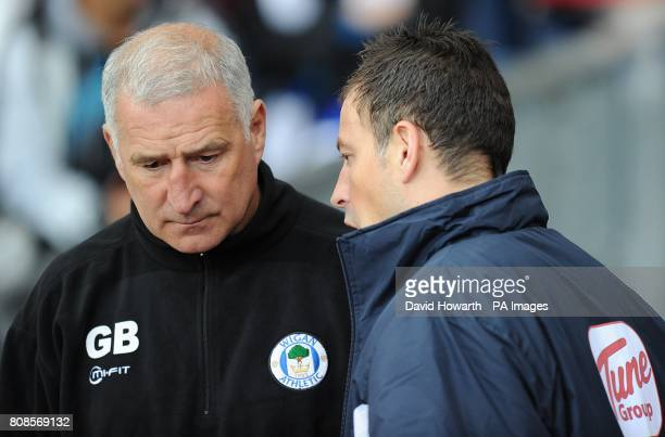 Fourth official for the day Mark Clattenburg chats with Wigan Athletic first team coach Graham Barrow before the match