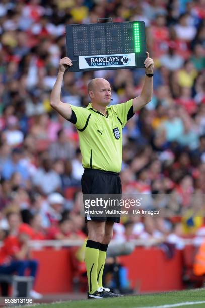 Fourth official Lee Mason holds up a Barclays Premier League LED substitute board to signal one minute of added time to be played