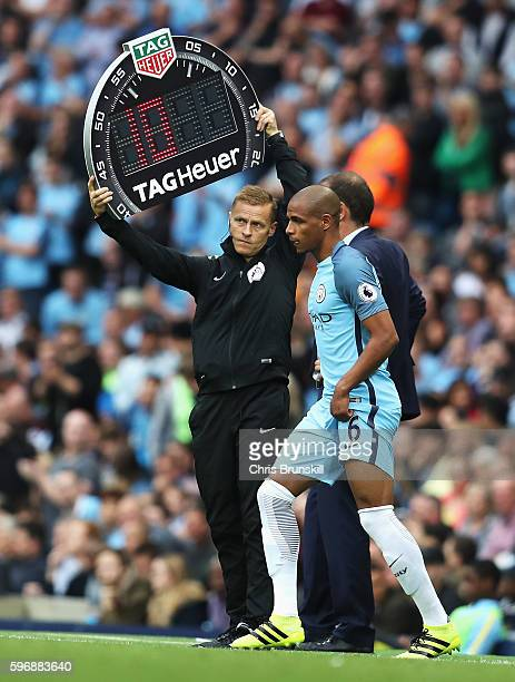 Fourth official Mike Jones holds the electronic board as Fernando of Manchester City comes on as a substitute during the Premier League match between...