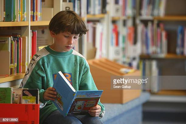 A fourthgrade student looks at books in the elementary school at the John F Kennedy Schule duallanguage public school on September 18 2008 in Berlin...