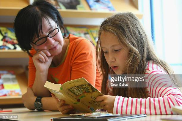 A fourthgrade student reads a book with her teacher in the elementary school at the John F Kennedy Schule duallanguage public school on September 18...