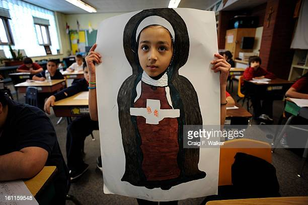 022410_CATHOLIC_CFW Fourthgrader Brittney Gonzalez displays the portrait she made of Saint Teresa of Avila for a report she is working on in her...