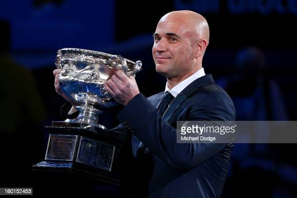 Fourtime Australian Open men's singles champion Andre Agassi carries the Norman Brookes Challenge Cup ahead of the men's final match between Novak...