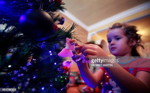 Fouryear old Spanish Vera Martin prepares the Christmas tree at her home on the Spanish Canary island of Tenerife on December 8 2013 AFP PHOTO/...