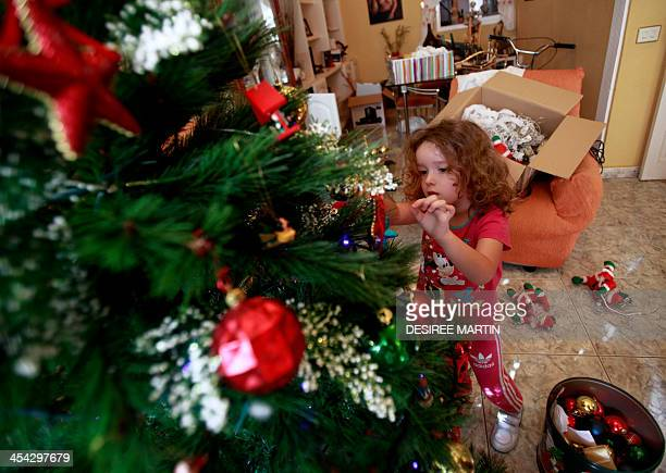 Fouryear old Vera Martin prepares the Christmas tree at her home on the Spanish Canary island of Tenerife on December 8 2013 AFP PHOTO/ DESIREE MARTIN